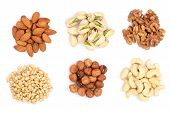 Mixed Of Nuts Heap Isolated On White Background. Almonds, Cashews, Hazelnuts, Pine Nuts And Walnuts. poster