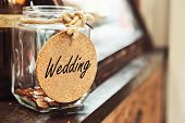Vintage Retro Glass Jar With Hemp Rope Tie Wedding Tag And Few Coins Inside On Wood Counter Concept  poster