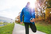 Young Runner In Blue Jacket Outside In Colorful Sunny Autumn Nature Standing On An Asphalt Path, Str poster