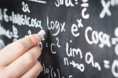 Professor Writing Mathematical Formula And Equation To Blackboard In School Classroom. College Or Un poster