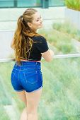 Back View Of Young Teenage Woman Wearing Short Blue Jeans Denim Shorts Enjoying Summer Weather poster
