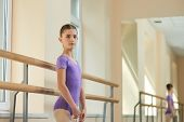 Young Beautiful Ballerina Posing In Studio. Caucasian Young Girl Standing Near Ballet Barre During B poster
