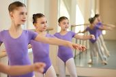 Young Caucasian Ballerinas In Ballet Class. Beautiful Little Ballerinas Training At Ballet Barre In  poster