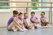 Little Ballerina Showing Her Ballet Shoes To Colleagues. Beautiful Young Ballet Dancer Sitting On Th poster