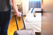 Man Pulling Suitcase And Entering Hotel Room. Traveler Going In To Room Or Walking Inside Motel With poster