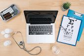 Top View Of Doctor Desk Table With Stethoscope And Notebook With A Visual Test Chart poster