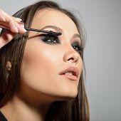 Young beautiful model applying makeup. Fashion girl with mascara. Eyelash makeup. Fashion girl. poster