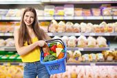 Young woman with basket shopping in supermarket poster