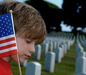 stock photo of bereavement  - Child with an American Flag in a Military Cemetery - JPG