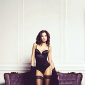 Sexy And Beautiful Woman In Erotic Lingerie And Stockings Posing On A Violet Sofa In Vintage Interio poster