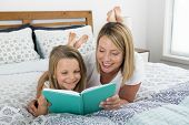 Young Blond Caucasian Woman Lying On Bed With Her Young Sweet  7 Years Old Daughter Reading Book Tog poster