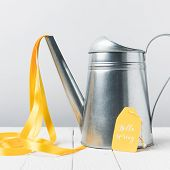 Close-up View Of Shiny Watering Can With Yellow Ribbon And Hello April Lettering On Tag poster