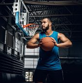 Portrait Of Black Basketball Player Holds A Ball Over A Hoop In A Basketball Hall. poster