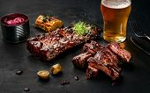 Pork And Beef Ribs In Barbecue Sauce And A Glass Of Beer On A Black Slate Dish. A Great Snack To Bee poster