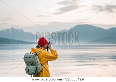 poster of Traveler Photographer Wearing Yellow Raincoat Taking Photo By Professional Camera Of Fantastic Scand