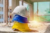 White, Blue And Yellow Hard Safety Helmet For Safety Accident Stack On Floor At Workplace In Constru poster