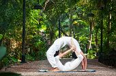 stock photo of dhanurasana  - Couple Yoga of man doing chakrasana and woman doing dhanurasana poses in white cloth in the garden - JPG