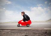 Постер, плакат: Молодой предприниматель вождение автомобиля игрушки на дороге