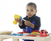 stock photo of work bench  - Closeup image of an adorable toddler playing carpenter with plastic tools on a work bench - JPG