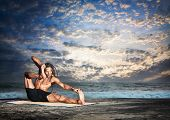 foto of dhanurasana  - Yoga akarna dhanurasana archer pose by fit man with dreadlocks on the beach in the evening at ocean background - JPG