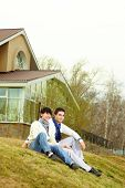 Tilt up of stylish homosexual lovers sitting on the grass in front of the townhouse