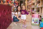 Cute Little Girl With Her Mom Go Into Toy Store. Happy Kid Choosing Toys With Mother. Mom And Daught poster