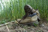 Pair Of Old Worn Leather Hiking Boots An A Gravel Path Or Road Balanced On Top Of One Another In A C poster