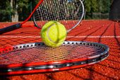 Tennis Scene With Black Net Shadow, Tennis Ball Resting On Top Of A Tennis Racquet On Red Hard Court poster