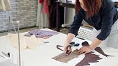 Cutting And Sewing Products In Tailoring Business. Tailor Woman Cutting Details From Fabric Works In poster