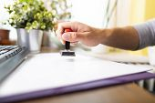 Man At Work In The Office, At The Desk. A Male Hand Holding A Rubber Ink Stamp. Man Stamps Documents poster
