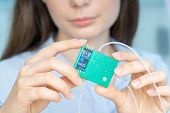 Young scientist woman in microbiological lab with lab-on-chip LOC microfluidic device poster
