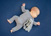 Charming newborn sleeping on back near toy poster