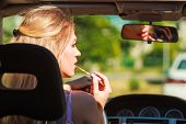 Concept Of Danger Auto Drive. Young Woman Driver Painting Her Lips Doing Applying Make Up While Driv poster