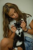 Pretty Young Caucasian Girl With Cute Kitten. Teenager Girl With A Wary Kitten. A Child And A Cat. A poster