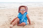 A Little Girl In Blue Pareo, Sunglasses And A Hat Sits On The Golden Sand On The Beach By The Sea. T poster