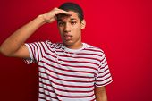 Young handsome arab man wearing striped t-shirt over isolated red background worried and stressed ab poster
