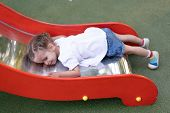 Little Caucasian Girl Lies On A Slide At The Playground Tired Of A Sad Summer Day. Chilhood. Tired C poster