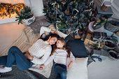 Happy Mother And Daughter Opening Christmas Gifts. Family Gathered Around A Tree At Home. Christmas  poster