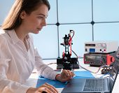 A young woman writes an algorithm for the robot arm. Science Research Laboratory for Robotic Arm Mod poster