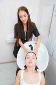 Hair Stylist Washing Woman Hair In Salon poster