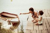 stock photo of child feeding  - Lovely mother and daughter feeding gooses on the lake - JPG