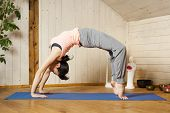 picture of dhanurasana  - An image of a pretty woman doing yoga at home  - JPG