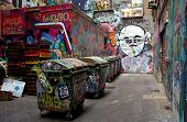stock photo of street-art  - alley with bins and walls covered in graffiti - JPG