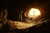image of cave  - man standing in front of a cave entrance - JPG