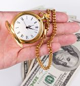 picture of currency  - hand holding a watch with money in the background - JPG