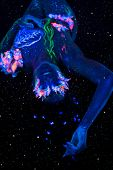 pic of uv-light  - Beautiful lying woman with body art glowing in ultraviolet light - JPG