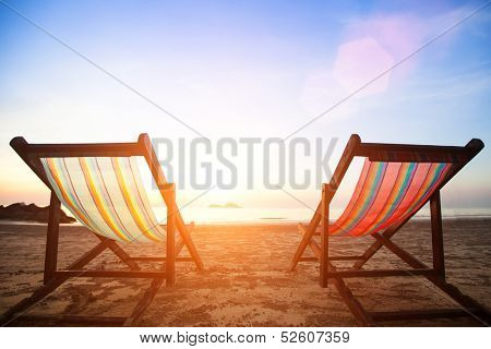 Beach chairs on the evening sea coast. poster