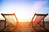 stock photo of sunny beach  - Beach chairs on the evening sea coast - JPG