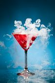 red cocktail with ice vapor, blue background