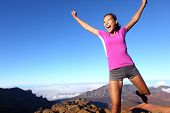 Success winner fitness runner woman jumping happy, excited and energetic with happy cheering face ex